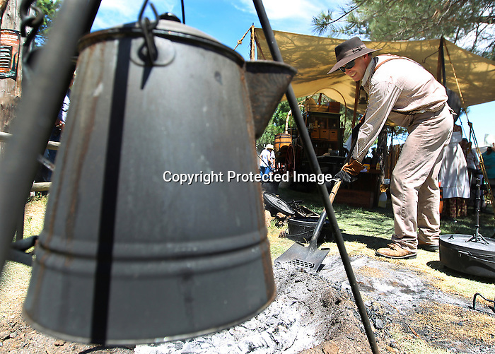 A coffee kettle heats up as Chuckwagon chef Mike Stallard shovels coals during the Chuckwagon Cook-off Championship at Frontier Park Saturday. Michael Smith/staff
