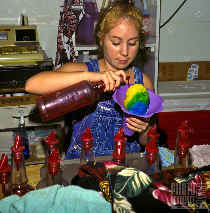Girl preparing shave ice, delicious local treat in Hawaii made with ice and flavored syrup
