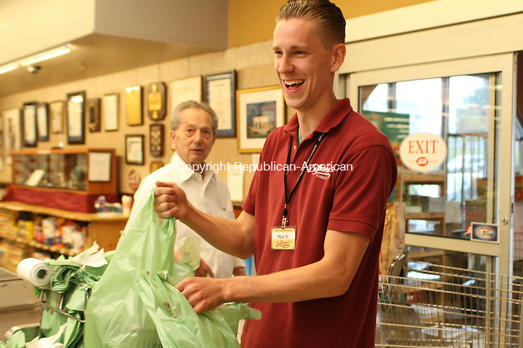 WATERTOWN, CT, 15 August 2014-081514LW06 - Matt Noonan, left, bags groceries at LaBonne's Market on Straits Turnpike in Watertown Friday. Noonan recently won a New England bagging competition. Laraine Weschler Republican-American