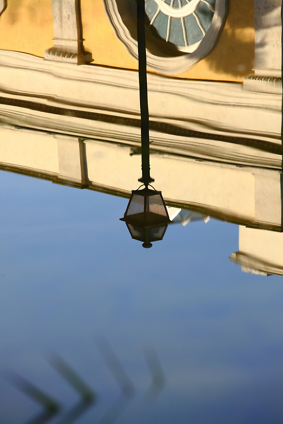 Rome, villa Torlonia: The reflected image of the top part of the old main building (with the half of a circular window) and of a street lamp in the nearly flat (apart from a pleating) water surface of the near basin in villa Torlonia. In fact, the image is slightly distorted.