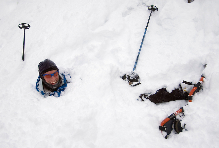 A snowshoer is engulfed in deep powder after jumping off a steep cliff deep in the woods north of Ishpeming, Michigan.