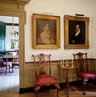 A pair of gilt-framed portraits in oil hangs above a pair of antique chairs in the hallway