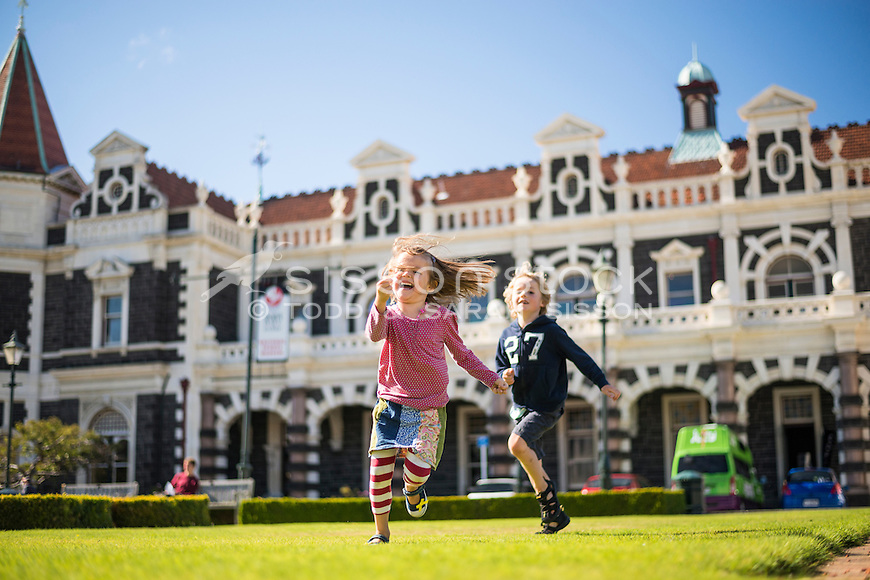 Young boy and girl (brother and sister) laughing and chasing each other on the grass outside the historic Dunedin Railway Station on a sunny blue sky day, Otago, South Island, New Zealand - stock photo, canvas, fine art print