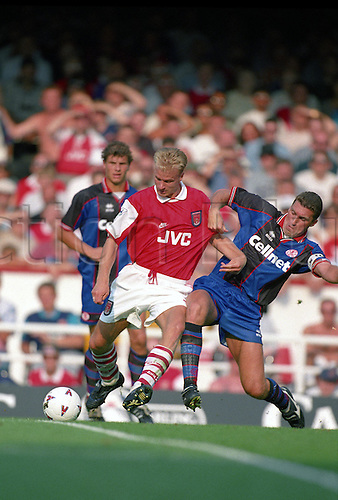 20 August 1995: Arsenal striker Dennis Bergkamp is challenged by Nigel Pearson during the Premier League match between Arsenal and Middlesbrough at Highbury. The  match was drawn 1-1. Photo: Glyn Kirk/Actionplus.950820 football soccer man men player footballer tackle tackling.