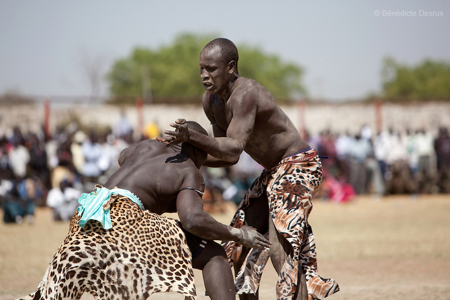 18 december 2010 - Juba, Southern Sudan - Traditional wrestling final tournament match in Juba Stadium between Dinka wrestlers from Bor, Jonglei State and Mundari wrestlers from Central Equatoria State. The matches attracted large numbers of spectators who sang, played drums and danced in support of their favorite wrestlers.The matches attracted large numbers of spectators who sang, played drums and danced in support of their favorite wrestlers. The match organizers hoped that the traditional sport would bring together South Sudan's many different tribes. Photo credit: Benedicte Desrus