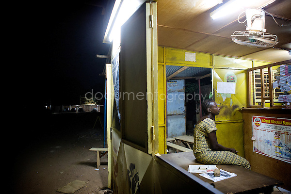 10:45 pm, while watching an American movie with Arabic subtitles Mamounata waits for the last customer. At 11 pm, she will close the club having cleaned up the floor in front of the kiosk.
