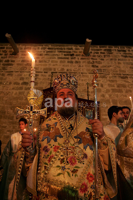Christian Orthodox  hold up candles lit from the 'Holy Fire' as thousands gather in the Church in Gaza City on April 24, 2011. Photo by Mohammed Othman