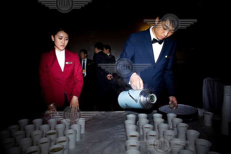 Attendants prepare tea for delegates at the Great Hall of the People during the Chinese People's Political Consultative Conference (CPPCC), plenary session for the NPC (National People's Congress).