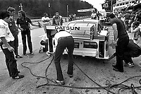 Sam Posey (2nd from left) listens while a crew member discusses the Datsun 280 ZX Turbo before practice for the Camel GT IMSA race at Road America near Elkhart Lake, Wisconsin, on August 31, 1980. (Photo by Bob Harmeyer)