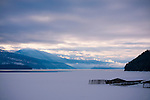 Idaho, Priest Lake, Morning sun rays over the Selkirk Mountains with partially frozen Priest Lake from Elkins Resort on Reeder Bay.