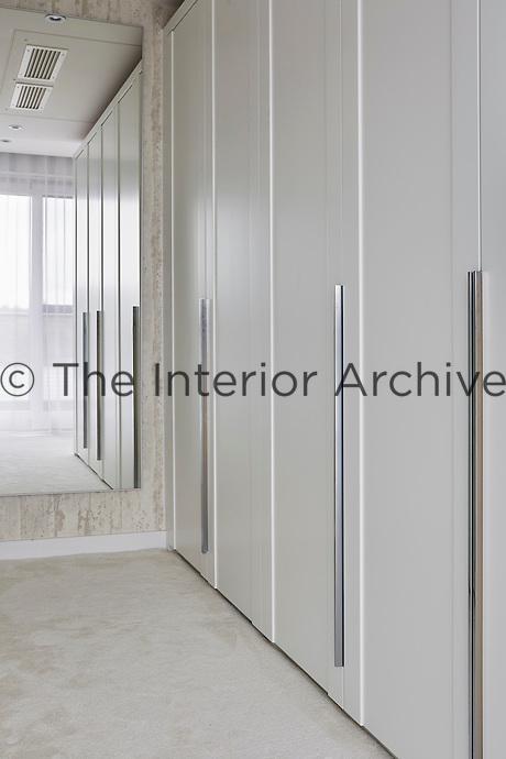 The elegant, bespoke wardrobes provide plenty of storage space in the dressing room.