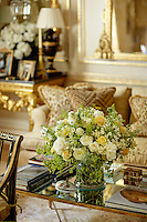 An arrangement of yellow and white roses is displayed on a mirrored table in a luxurious sittng room.