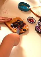 Girl age 5 making peanut butter and jelly sandwich.  Western Springs  Illinois USA