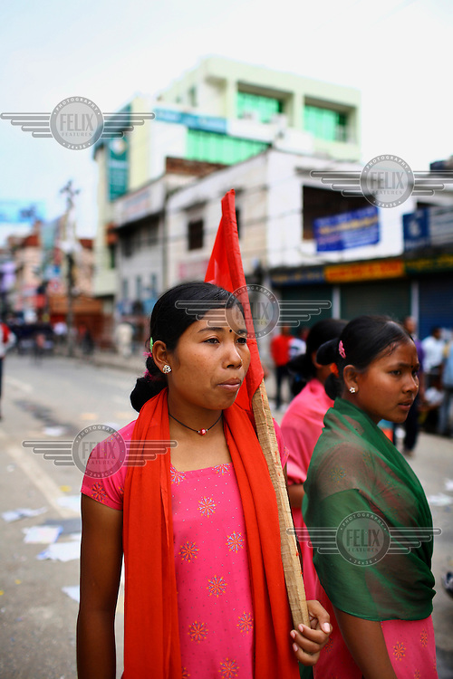 A woman carries a flag as she protests at a strike called by the Unified Communist Party of Nepal (UCPN) to remove the ruling government. The Maoist opposition blocked streets leading to key government offices on the 6th May, the fifth day of their crippling general strike to demand the prime minister's resignation, but the government has vowed not to bow to the protesters' pressure. The Maoists, known to use violence to back their strike calls, have demanded that residents halt all travel and keep businesses and schools closed since Sunday in their campaign to get Prime Minister Madhav Kumar Nepal to resign and hand power to a Maoist-led government. The strike has shut down most businesses, schools and transport, with daily activity grinding to a standstill.