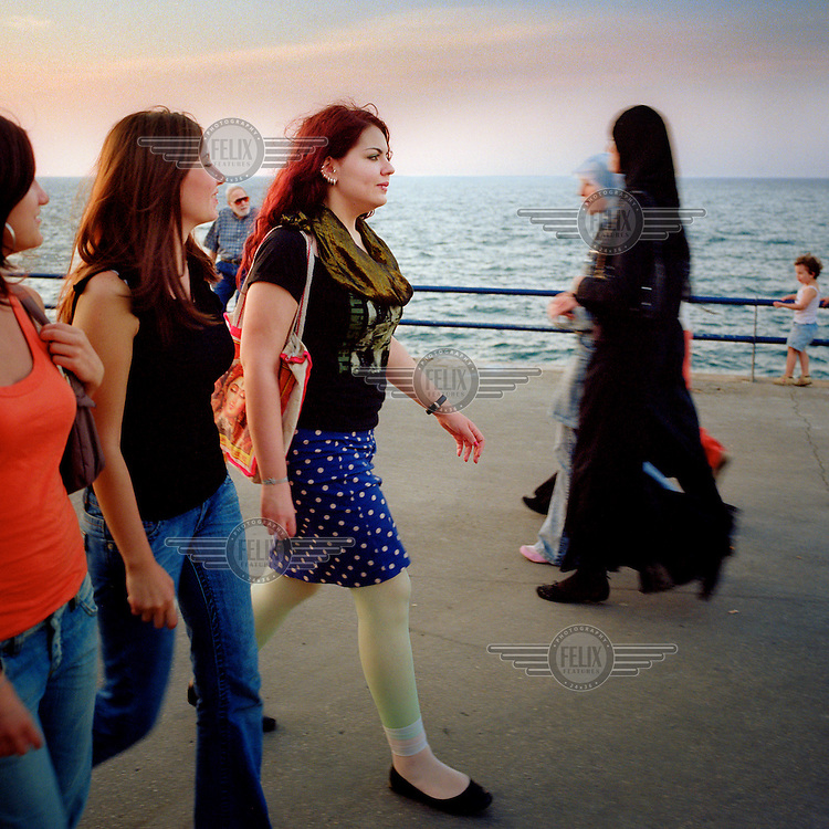 Theatre actress Taghrid Choucair (centre) walks along the Corniche seafront with her friends.