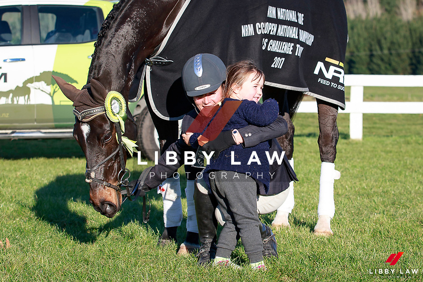Emily Cammock gets presented with her trophy from her daughter after taking the Title for the NRM CCI3* Open National Championship with Shaw Lee during the Prizegiving at the 2017 NZL-NRM National Three Day Event Championships. National Equestrian Center, Taupo. Sunday 14 May. Copyright Photo: Libby Law Photography