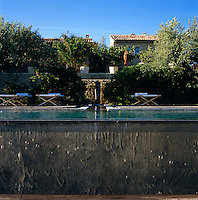The sun-loungers surrounding this infinity pool sit in the shade of olive trees on a terrace below the hotel