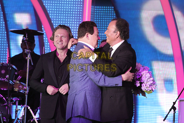 Julio Iglesias, Alexander Kogan, Iosif Kobzon <br /> &quot;New Wave International festival&quot;, Jurmala, Latvia, 24th July 2013.<br /> half length music live on stage concert gig black suit tie flowers hugging hug <br /> CAP/PER/UG<br /> &copy;UG/PersonaStars/CapitalPictures