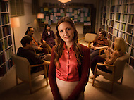 A female counselor stands in front of a group in session.