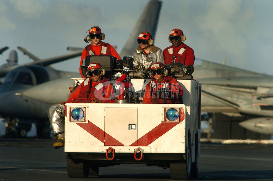 040818-N-6213R-108 Western Pacific Ocean (August 18, 2004) - Members of the Air Departments Crash and Salvage  division re-position their P-25 Firefighting Tractor on the flight deck aboard USS John C. Stennis (CVN 74). The P-25 is filled with 60 gallons of water along with 750 gallons of Aquious Film Forming Foam (AFFF) to fight an aircraft fire. The ship and Carrier Air Wing Fourteen (CVW-14) are currently at sea on a scheduled deployment. Photo by Mark J. Rebilas