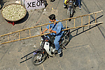 Asia, Vietnam, Ho Chi Minh City (Saigon). Asian man transprting a leddar by motorbike along Bui Vien St. in the backpackers area around Pham Ngu Lao / Bui Vien St. (District 1).