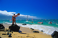 Children enjoy watching windsurfers at Kanaha Beach Park, which is popular with both windsurfers and kitesurfers on Maui's North Shore.