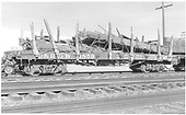 Side view of D&amp;RGW flatcar #1859 at Alamosa loaded with remains of destroyed gondola #9605(?) which had been used as an idler flatcar on pipe trains.<br /> D&amp;RGW  Alamosa, CO  Taken by Richardson, Robert W. - 10/1950