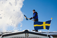 Sweden, SWE, Kiruna, 2008MAR20: A man clears the snow off the roof of his house.