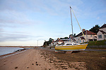 Sailing boat dumped on beach by winter storm surge December 2013, Bawdsey, Suffolk, England