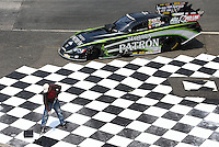 May 29, 2013; Englishtown, NJ, USA: A painter touch up paints a checkered flag in the winners circle near the car of NHRA funny car driver Alexis DeJoria at Raceway Park. Mandatory Credit: Mark J. Rebilas-