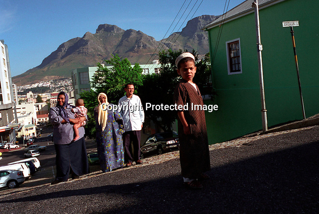 dippfamil00005 .People Family. Fejrus with baby and Miriam (old woman) and Husband of Fejrus and their son (foreground) on November 29, 2002 outside their current home in Bo-Kaap, a muslim area in central Cape Town, South Africa. Miriam is one of the first people that will return to Distrixt 6, an area in central Cape Town where they were forced out of during the old apartheid regime. New houses are soon being built..©Per-Anders Pettersson/iAfrika Photos