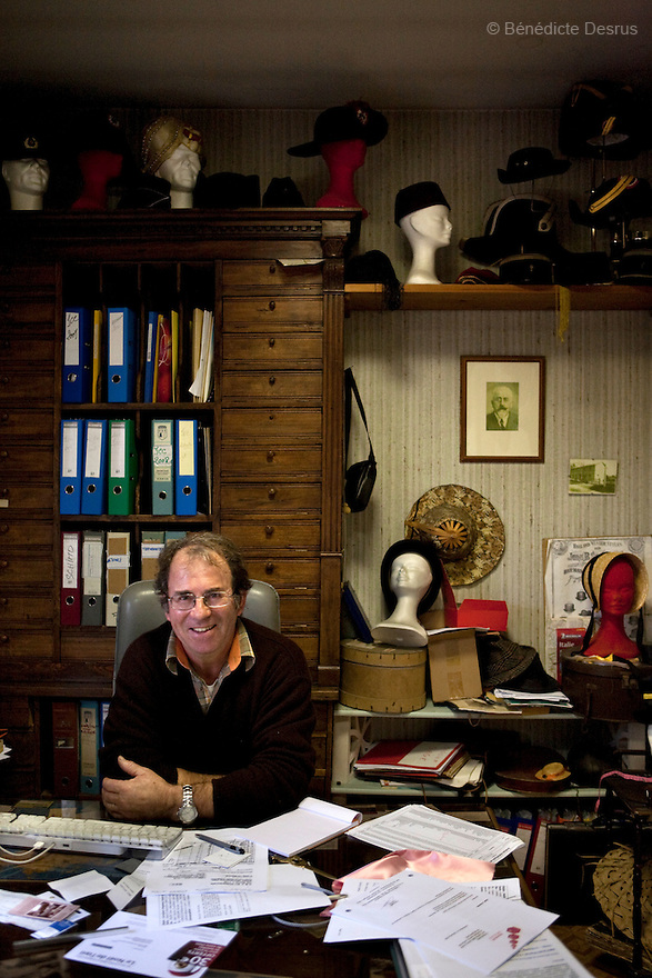 9 december 2009 - Coustilleres' hat factory, Septfonds, France - Jean-Claude Coustilleres in his office at the Coustilleres' hat factory. behind him his collection of hats from all over the world..Septfonds is the heart of French straw hat making, due to its very ancient hatter tradition. The hat making industry had its commercial peak in the late 19th century..Coustillères is a family owned hat making factory that has been making straw hats in Septfonds for nearly 100 years. They make hats from straw, felt, and cloth as well as caps. The current owner is Jean-Claude Coustilleres. He is one of the last hat makers of the region..The straw hat making process is very labor intensive and numerous hands are involved. Nearly all of the equipment is over 100 years old, they use the original presses and tools including aluminium molds and sewing machines and dye their own straw continuing the traditional methods of manufacturing. The hat blocking and shaping, straw braids construction and dyeing are all done by hand..The company works on behalf of fashion houses and makes a variety of regional and historical hats. It produces 2 collections a year distributed by a network of salespeople and through a catalog to clients around the world. Photo credit: Benedicte Desrus