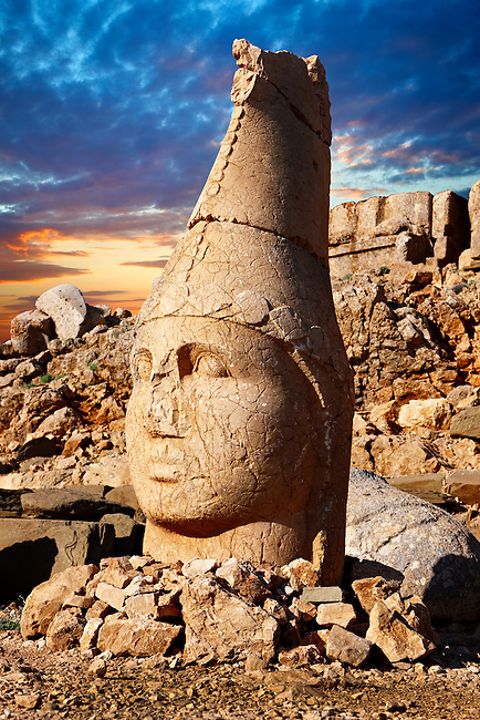 Picture & photo of the statues of around the tomb of Commagene King Antochus 1 on the top of Mount Nemrut, Turkey. Stock photos & Photo art prints. In 62 BC, King Antiochus I Theos of Commagene built on the mountain top a tomb-sanctuary flanked by huge statues (8–9 m/26–30 ft high) of himself, two lions, two eagles and various Greek, Armenian, and Iranian gods. The photos show the broken statues on the  2,134 m (7,001 ft)  mountain. 4