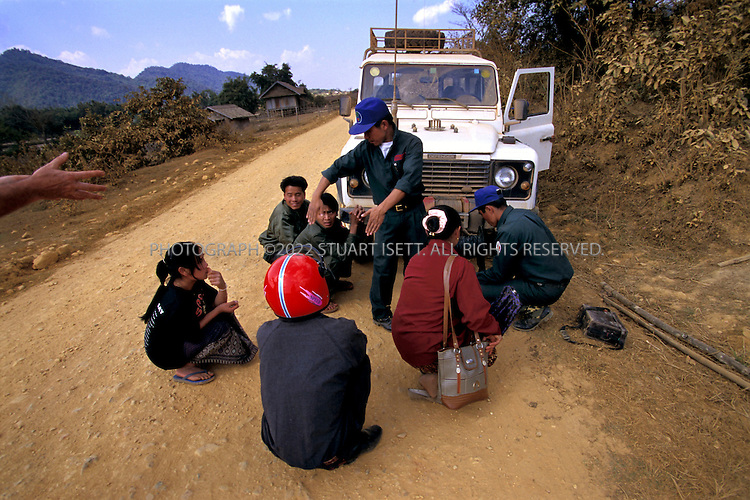 Phonsavan, Laos..MAG workers try to get villagers to take cover as MAG prepares to destroy an American bomb found by the side of this road. 30 years after the end of the war, Laotians are still be terrorized by American bombs...All photographs ©2003 Stuart Isett.All rights reserved.