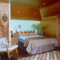 In the bedroom the walls are painted a warm ochre colour matched by retro furniture and shimmering bed linen