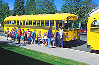 Elementary school children boarding school bus, Mount Shasta, California