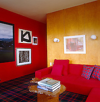David Netto's office has been painted fire-engine red with a matching red sofa and tartan carpet