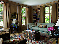The oak-panelled library has windows on two sides and is comfortably furnished