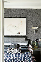 The bedroom is decorated in monochrome shades with soft textures such as the tweed wall covering.  Feminine touches of soft green and pink, give the overall design a 'dandyish' feel. A wall light hangs above a bedside table and the bed is piled with cushions.