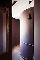 The pendant light in this curved corridor is by Tom Dixon and the carpet is a striped wall-to-wall design