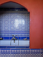 The bathroom is entirely in the Moroccan style with blue-and-white tiled walls and the bath set in an arched alcove