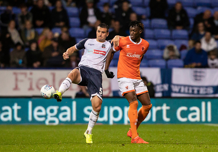 Bolton Wanderers' Jack Hobbs competing with Blackpool's Armand Gnanduillet (right) <br /> <br /> Photographer Andrew Kearns/CameraSport<br /> <br /> The EFL Sky Bet League One - Bolton Wanderers v Blackpool - Monday 7th October 2019 - University of Bolton Stadium - Bolton<br /> <br /> World Copyright © 2019 CameraSport. All rights reserved. 43 Linden Ave. Countesthorpe. Leicester. England. LE8 5PG - Tel: +44 (0) 116 277 4147 - admin@camerasport.com - www.camerasport.com