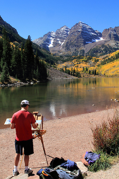 Caucasian male artist painting the Maroon Bells Peaks, near Aspen, Colorado, USA