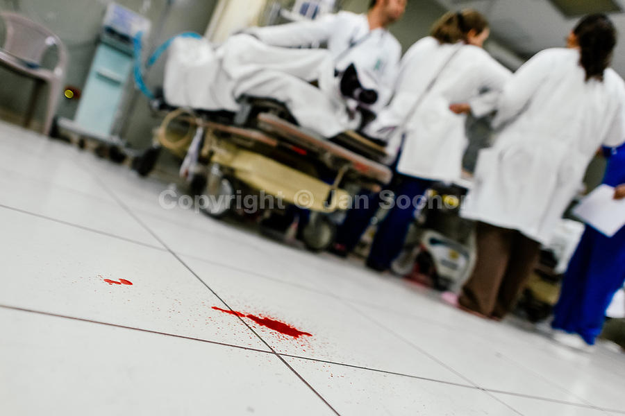 A pool of blood seen on the floor after providing an acute trauma resuscitation to a young gang member, with several gunshot wounds, in the emergency department of a public hospital in San Salvador, El Salvador, 16 December 2015.