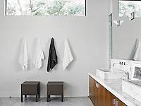 A row of towels hang on the bathroom wall below a long narrow window