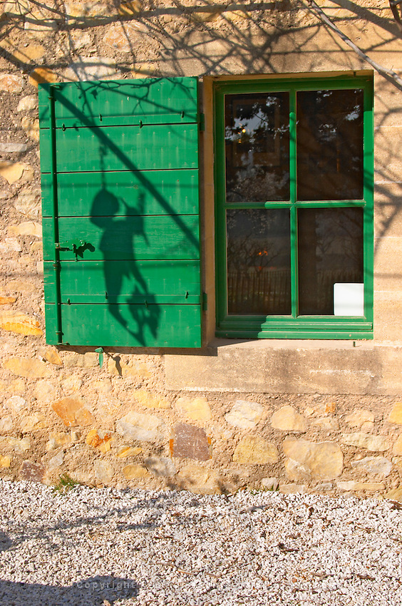 A window with a shadow of a sign with a vineyard worker on a green shutter at Mas de Gourgonnier, in Les Baux de Provence, Bouche du Rhone, France