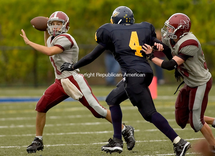 WATERBURY, CT- 27 SEPTEMBER 2008 --092708JS04--Naugatuck's Erich Broadrick (7) rolls out to pass while being pressured by Kennedy's Dionne Moffett (4) during their game Saturday at Municipal Stadium in Waterbury. <br /> Jim Shannon / Republican-American