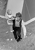 A dad carryng his little one up a grassy bank, Festival & Gala Day at the Education Centre, Wester Hailes, Scotland, 1979.  John Walmsley was Photographer in Residence at the Education Centre for three weeks in 1979.  The Education Centre was, at the time, Scotland's largest purpose built community High School open all day every day for all ages from primary to adults.  The town of Wester Hailes, a few miles to the south west of Edinburgh, was built in the early 1970s mostly of blocks of flats and high rises.