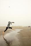 USA, Washington State, Long Beach Peninsula, International Kite Festival, woman jumps over the water to keep dry