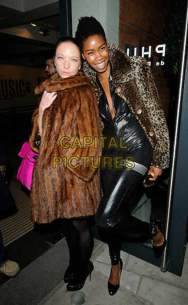 NATHALIE PRESS & TOLULA ADEYEMI.At the Destroy / Rankin Private View, Phillips de Pury & Co. Howick PLace, London, England, UK, .November 9th 2009..full length leopard print fur coat animal  black pvc shiny catsuit jumpsuit shoes Natalie brown knee leg up .CAP/CAN.©Can Nguyen/Capital Pictures.